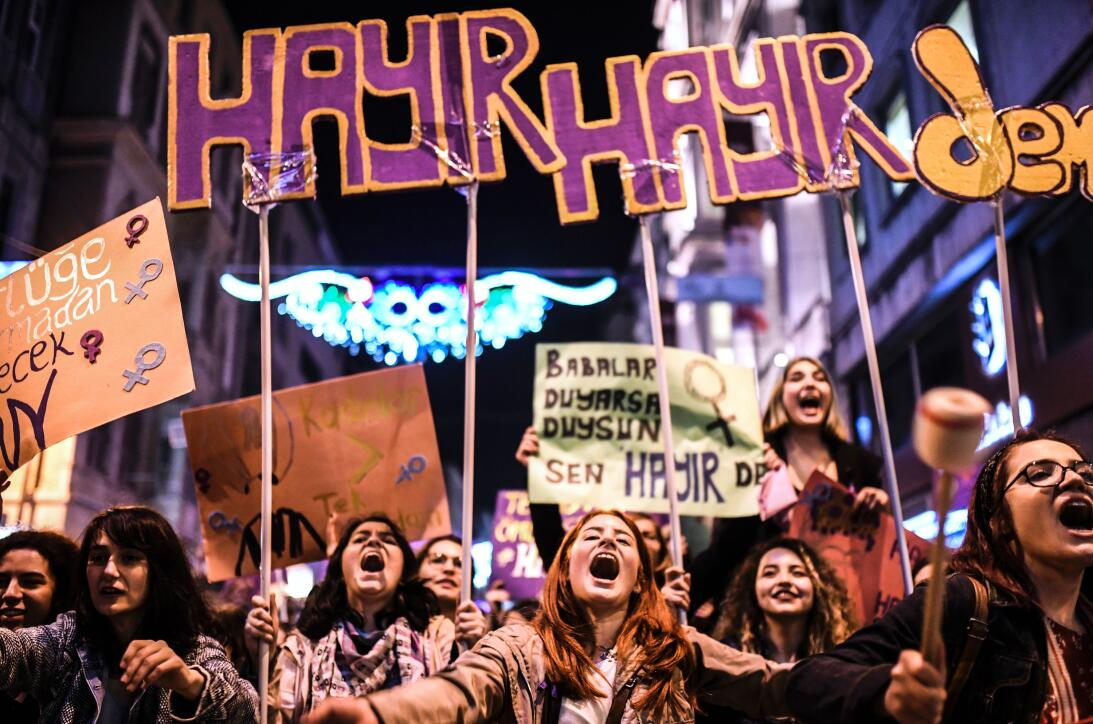 """People hold signs reading """"no"""" as they march down Istiklal Ave..."""