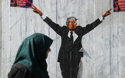 Una mujer musulmana pasa frentre a una imagen de Donald Trump