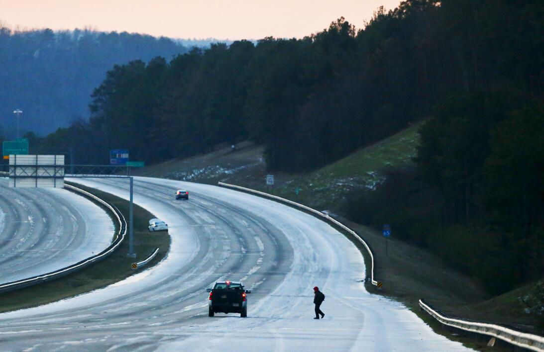 A person catches a ride on the icy highway after leaving their car on th...