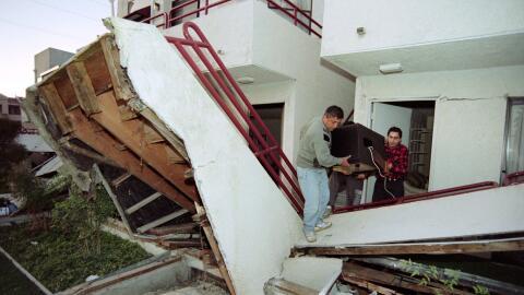 Una familia saca un televisor de un edificio dañado en sismo de Northridge.