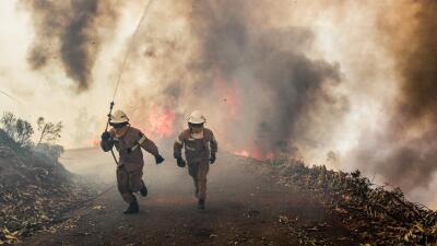 Dos bomberos huyen de las llamas en Capela Sao Neitel, Portugal, echando...