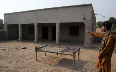 Un aldeano paquistaní posa mientras señala la casa donde u...