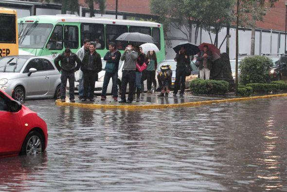 Un grupo de personas esperan cruzar la calle totalmente inundada. Se cub...
