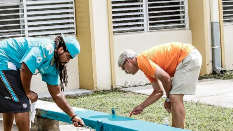Jugadores de los Miami Dolphins pintan los bancos de una escuela de Hial...