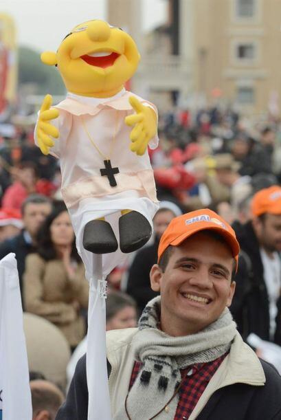 Un hombre sostiene una marioneta que llevaba un crucifijo delante de una...