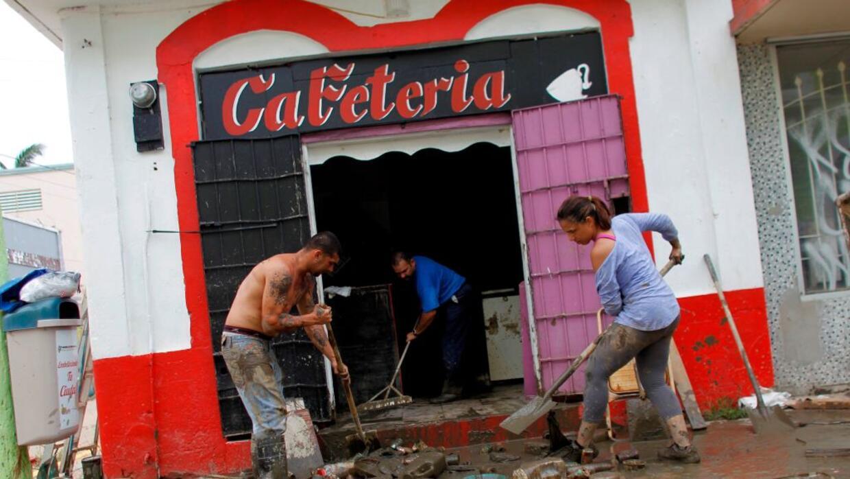 Empleados limpian un negocio que resultó dañado cuando el río Arecibo se...