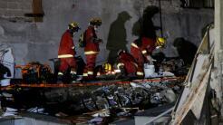Un equipo de rescate busca sobrevivientes en los escombros de un edifici...