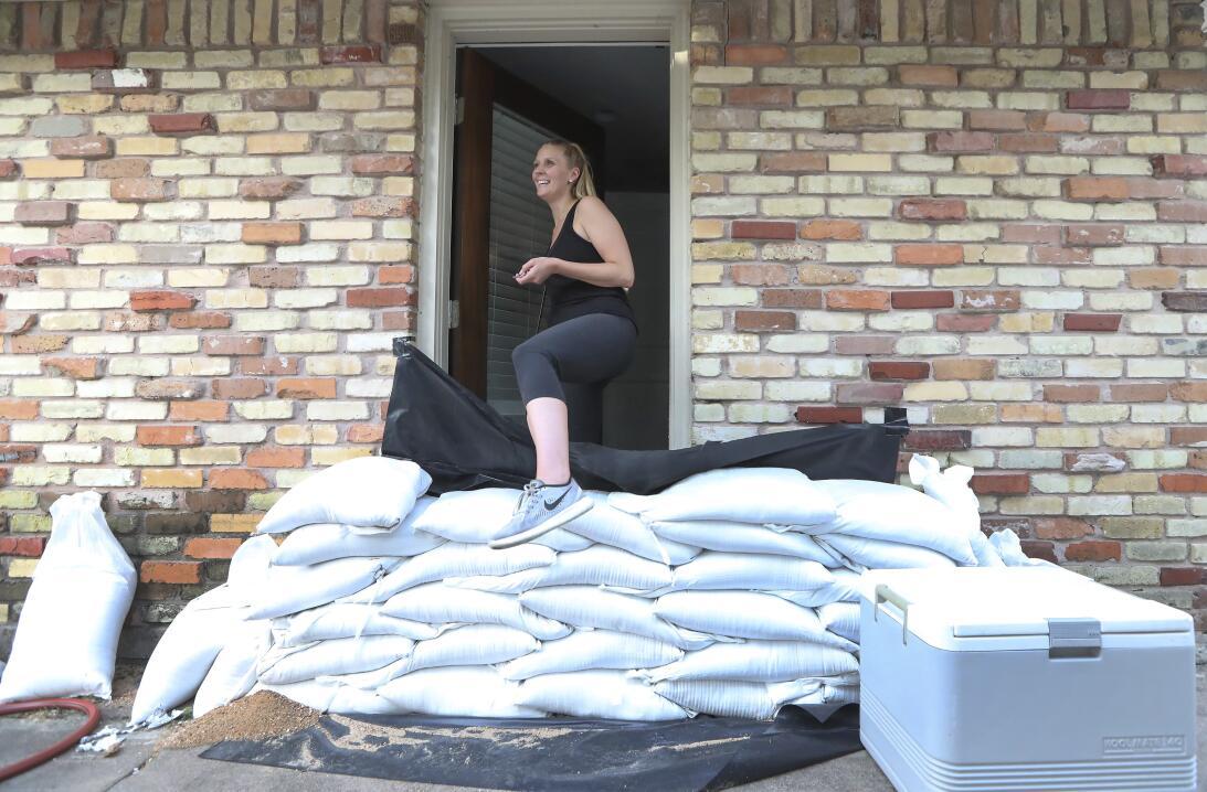 Lacey Williams sale de la puerta de su casa saltando los sacos de arena...