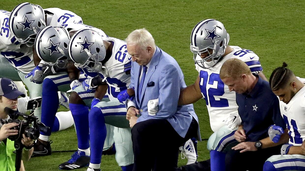 The Dallas Cowboys, led by owner Jerry Jones, center, take a knee prior...