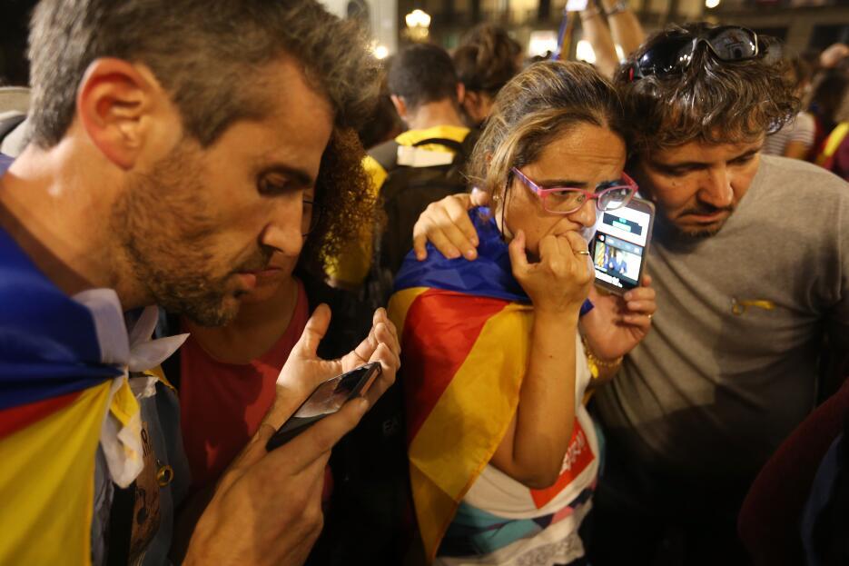 Un grupo de personas escucha con sus celulares el discurso del president...