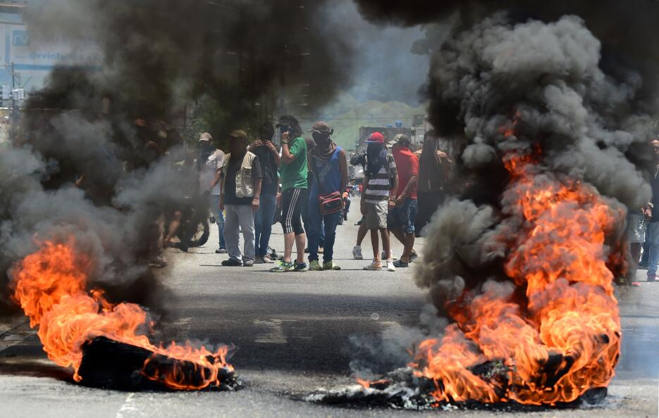 Manifestantes anti-gobierno tras una barricada en Valencia. Después de c...