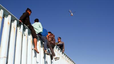 Migrantes desafían a las autoridades trepando el muro fronterizo en Tijuana
