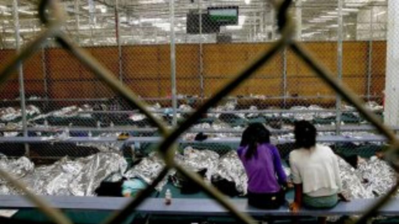 Dos niñas que cruzaron la frontera solas ven un juego de fútbol en uno d...