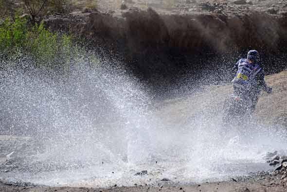 Los pilotos de las motos aprovechan el agua para refrescarse.