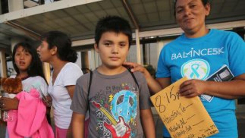 Una familia de inmigrantes salvadoreños espera un bus en McAllen, Texas,...