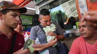 Un hombre carga bolívares para cambiar a pesos colombianos