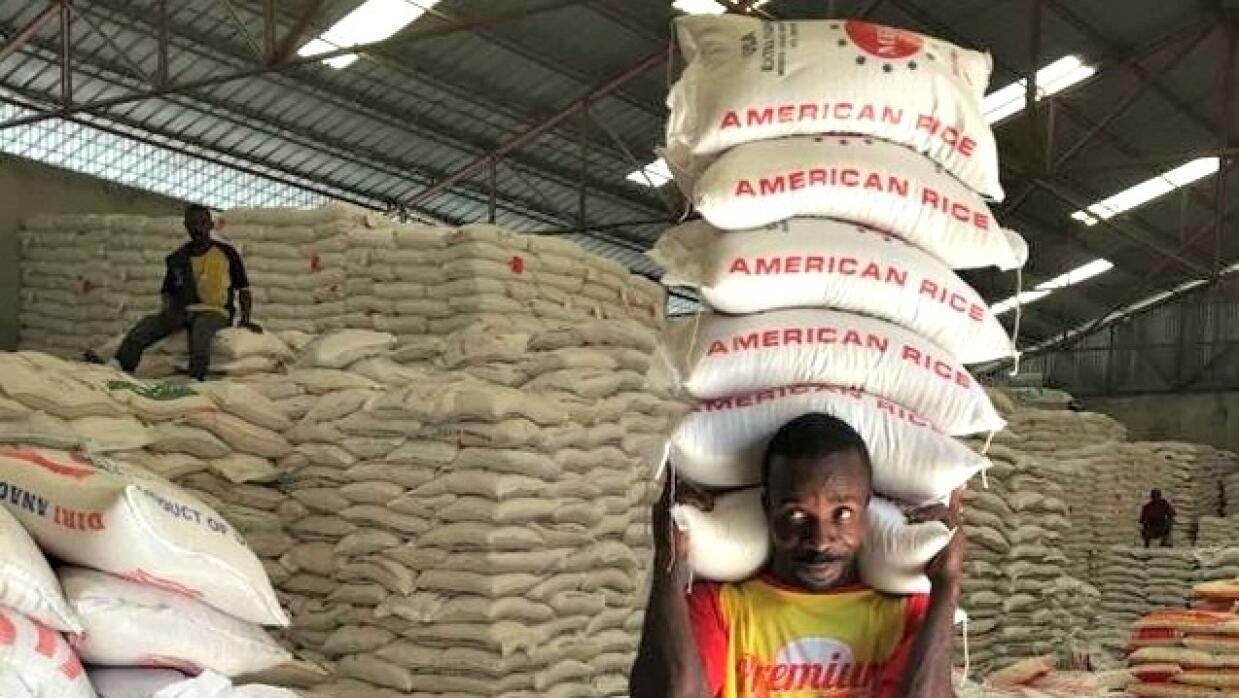 A man carries sacks of rice at a warehouse in the capital, Port-au-Princ...
