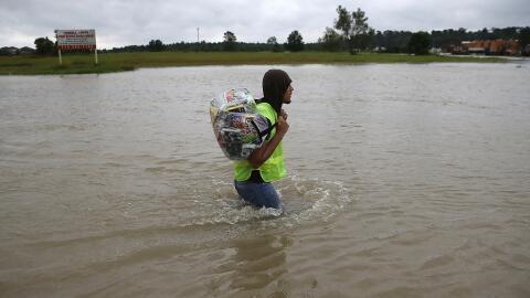 Un hombre carga un bolso con su ropa en el norte de Houston, zona afecta...