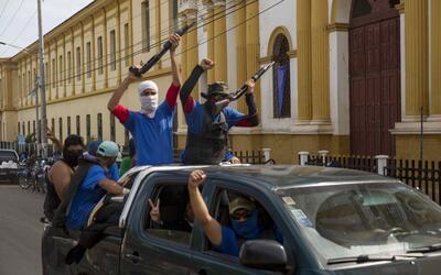 Personas con la cara tapada vigilan las calles hoy, miércoles 18...