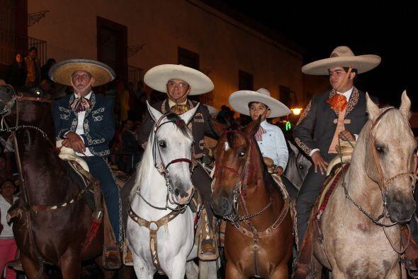 Tres hombres y un niño sobre sus caballos en esta tradición de las fiest...