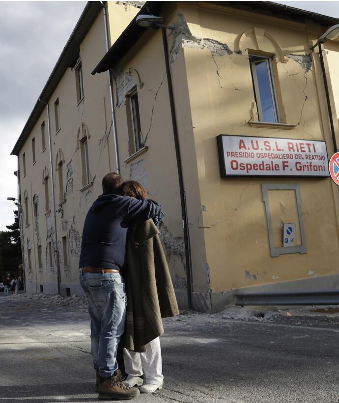 Este hombre abraza a una mujer frente al hospital de Amatrice, que sufri...