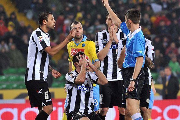 Maurizio Domizzi del Udinese le reza al árbitro para que no lo amoneste.