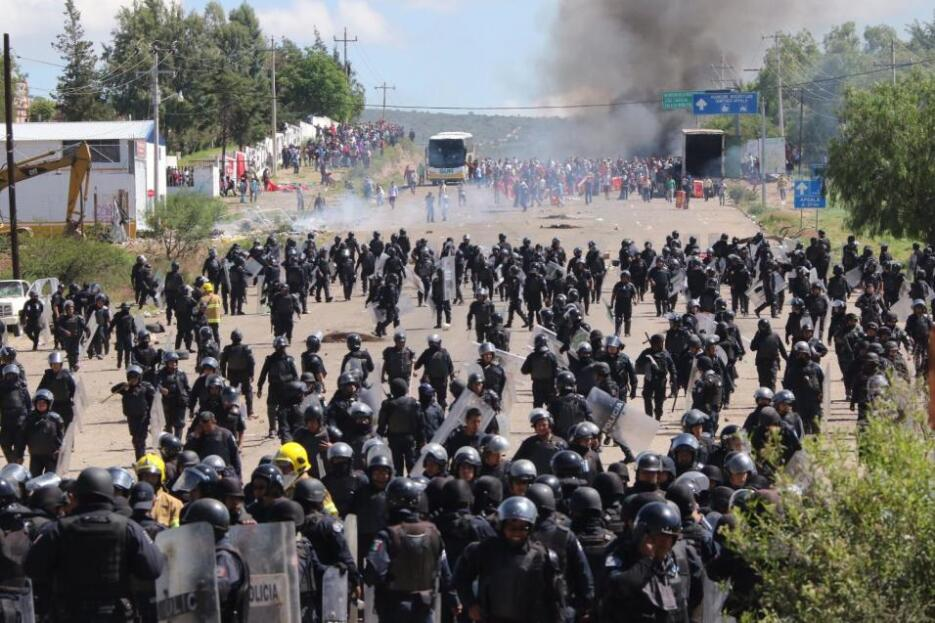 Riot police regroup during a clash with teachers