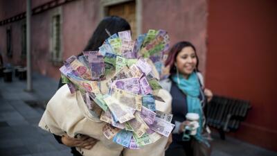 Una mujer carga un costal lleno de dinero durante una protesta en la Ciu...