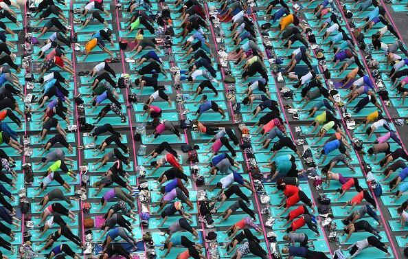 Una multitud de personas participa en una sesión masiva de yoga en Times...