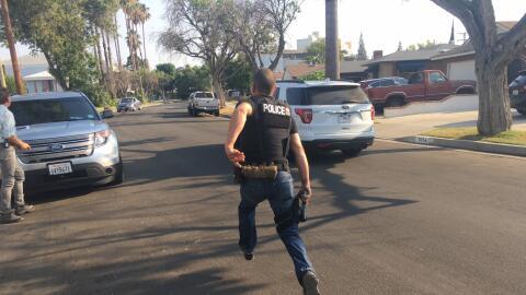 Un agente hispano corre tras un fugitivo en el vecindario Reseda, en el...