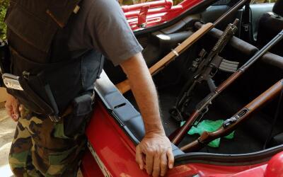 Un hombre armado se recarga frente a una camioneta en México (Ima...