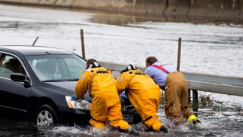 Bomberos de Long Island empujan un automóvil varado en una inundación.