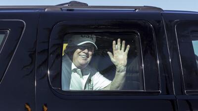 El presidente Donald Trump saluda a sus simpatizantes desde su caravana...