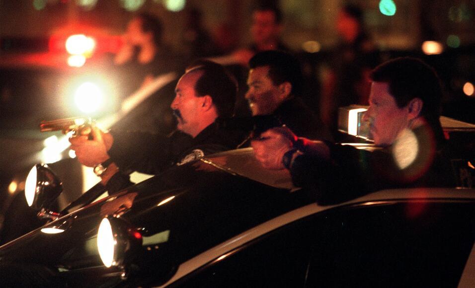 Agentes de la policía de Long Beach en California apuntan sus armas a un...