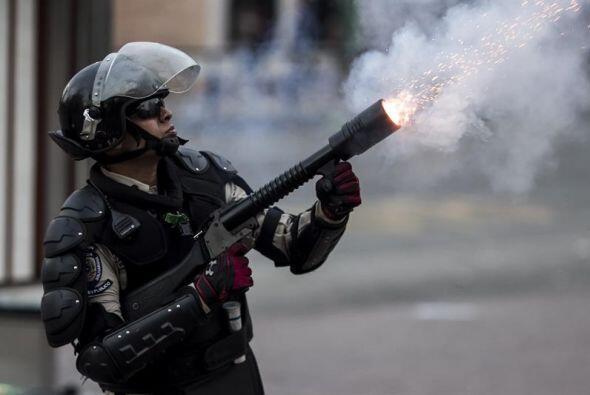 Un integrante de la Policía Nacional Bolivariana (PNB) lanza una...
