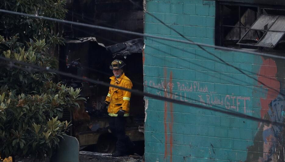 Un bombero sale del interior del almacén arrasado por las llamas en Oakl...