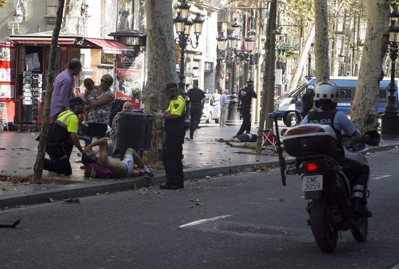 Personas heridas en el suelo son asistidas por personal de emergencias y...