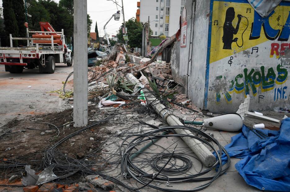 Un menor toma una fotografía al área que fue afectada tras el sismo en l...