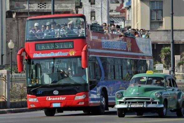 Un bus con turistas pasa junto a un taxi de época.