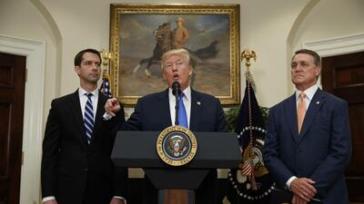 Donald Trump with Republican senators Tom Cotton (pictured left) and Dav...