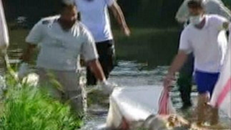 Dos hombres cargan un cadáver en uno de los barrios de Deir Ezzor, que f...