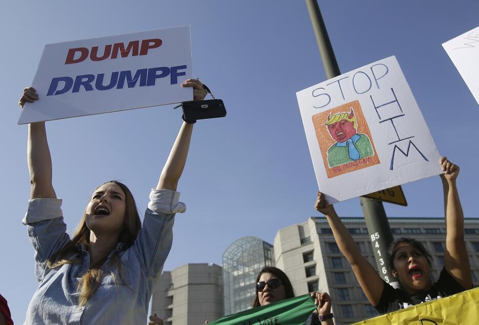 Varias mujeres sostienen carteles contra el candidato Donald Trump frent...