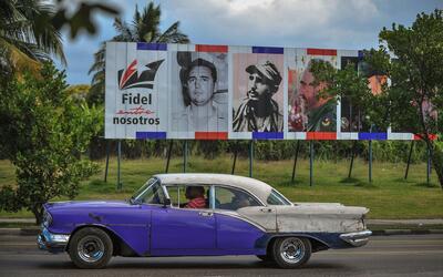 Un auto antiguo circula frente a una valla conmemorativa de Fidel en La...