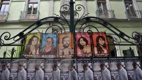 Vista de carteles con la imagen de las víctimas del homicidio m&u...