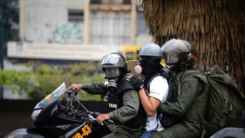 Soldados de la Guardia Nacional de Venezuela se llevan a un manifestante...