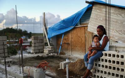 Una mujer con su bebé frente a su hogar dañado por el hura...