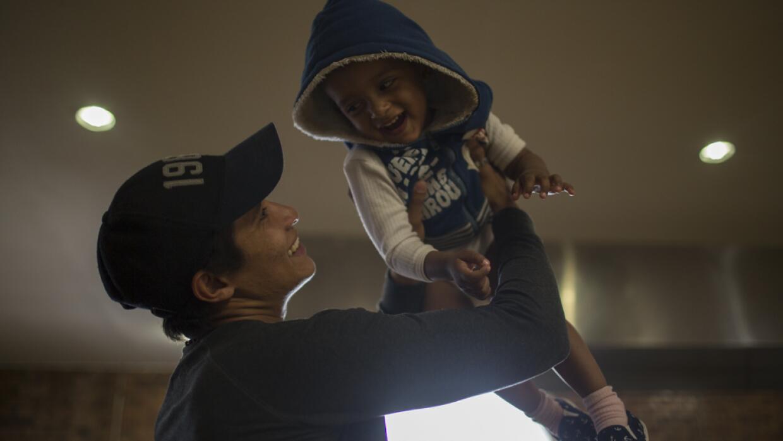 Luis, de 23 años, juega con su hijo en el comedor de la Casa del Migrant...