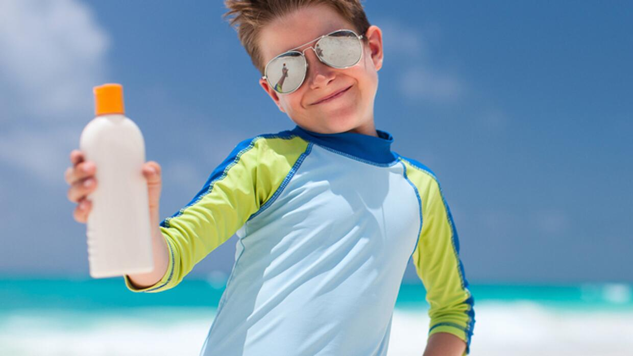 Boy on the beach with sunscreen