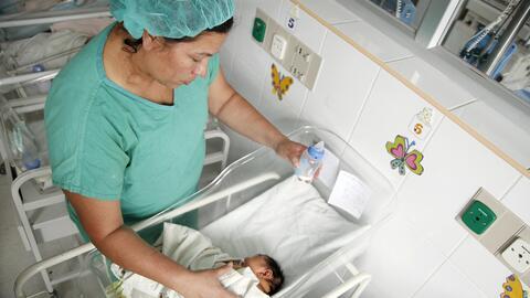 Una enfermera atiende un bebé con microcefalia, una malformación en el c...