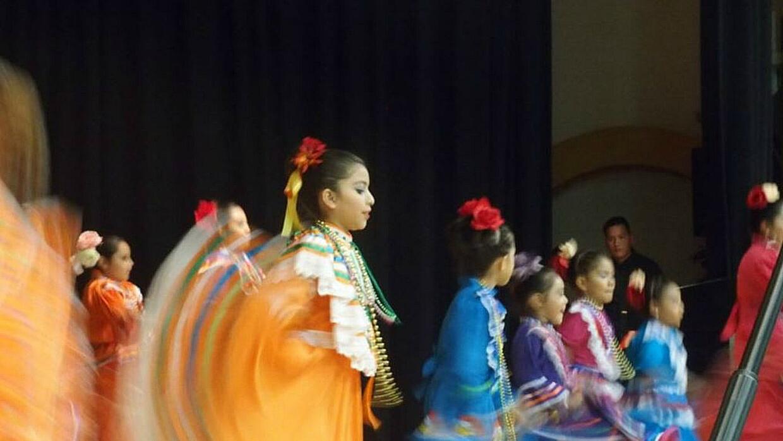 Estudiantes bailan con sus madres en una celebración del Mes de la Heren...